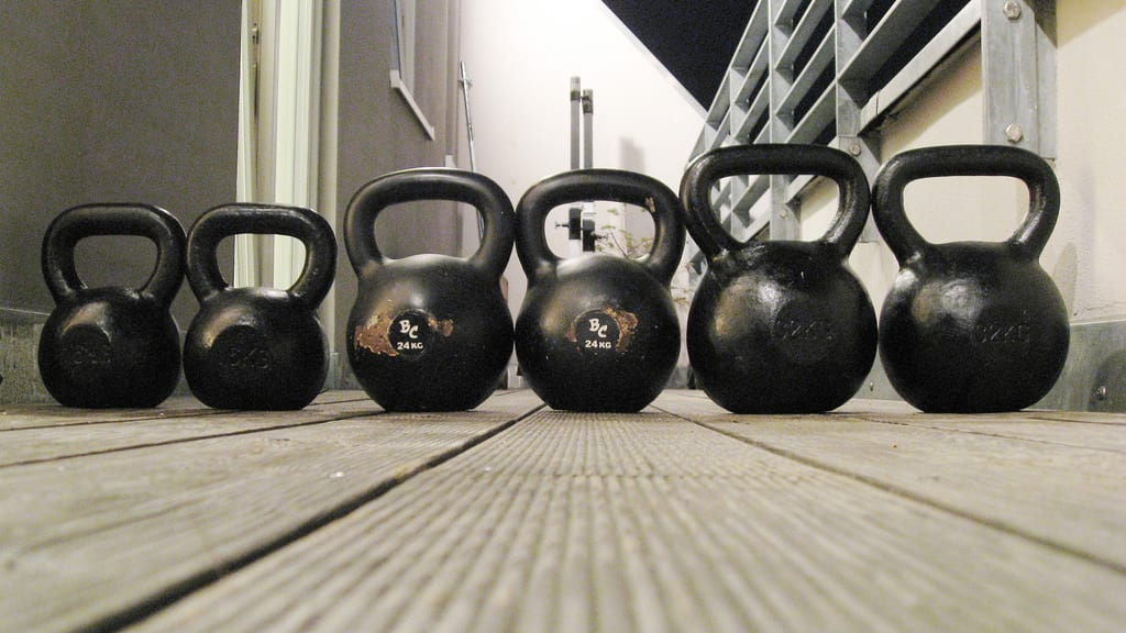 Kettlebells lined up on a deck icon https://www.GetStrong.fit/Fitness