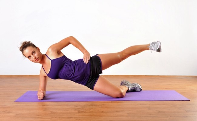 woman showing example on how to perform the kneeling side plank leg lift