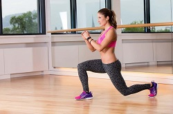 Woman performing a split lunge https://www.GetStrong.fit/Fitness