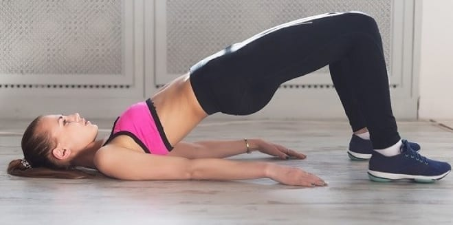 woman on the floor performing Glute Bridge Hold